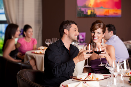 happy couple at restaurant table toasting